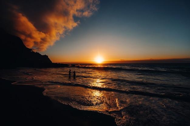 Счастливая веселая пара весело вместе бежит к морю и делает брызги воды на тропическом пляже на закате - понятие о романтическом отдыхе, медовом месяце.