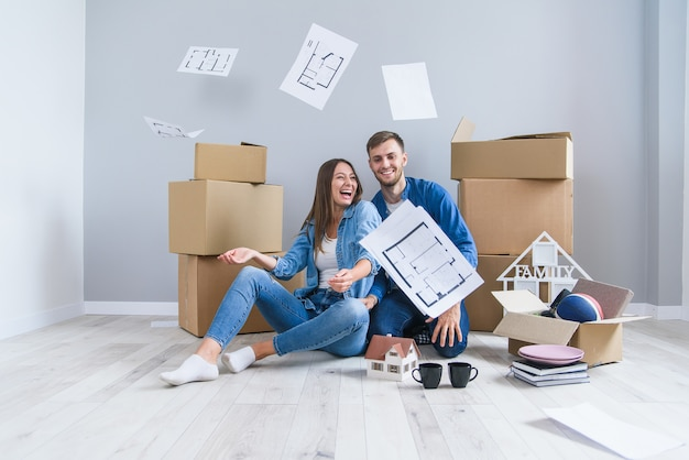 Happy cheerful couple in love having fun together in their own new flat after removing on the cardboard boxes