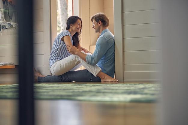행복 한 명랑 커플 바닥에 앉아 현대 집에서 함께 시간을 보내고