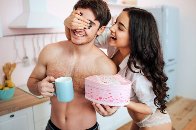 Happy cheerful couple stand in kitchen together. she covered his eyes with hand. woman give to man present. guy hold cup.
