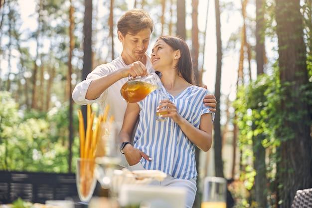 남자가 여자의 유리에 오렌지 레모네이드를 붓는 동안 행복 명랑 커플