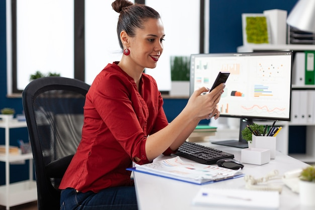 Happy cheerful excited businesswoman texting on smartphhone, sitting at desk in company workplace . entrepreneur messeging using mobile phone. employee reading text on phone.