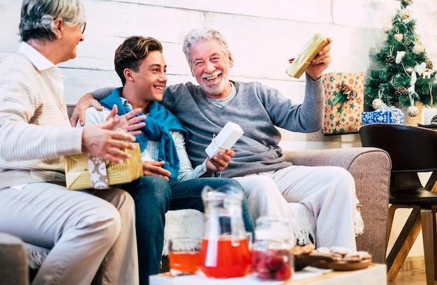 幸せな陽気な家族は一緒に楽しんで、贈り物を共有して休日とクリスマスイブを祝います