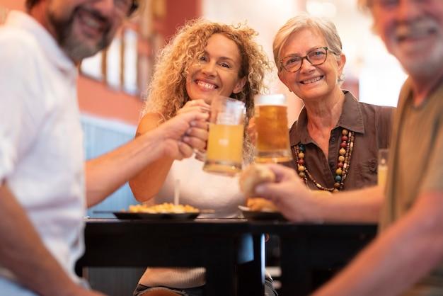 レストランのテーブルに座って一緒に楽しんで、ビールグラスをチリンと鳴らす幸せな陽気な家族。ビアグラスを乾杯し、レストランで祝う家族の肖像画