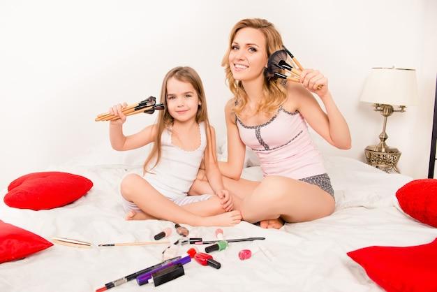 Счастливая веселая семья, сидя на кровати и показывая кисти для макияжа