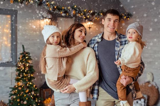Счастливая веселая семья ждет нового года на улице на фоне деревянного дома
