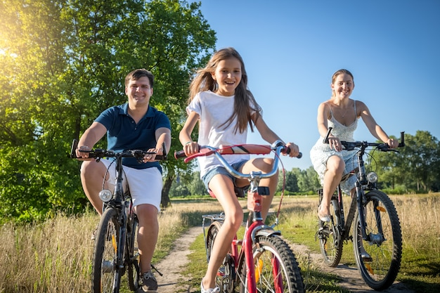 Happy cheerful family with daughter riding bicycles in meadow at sunny day