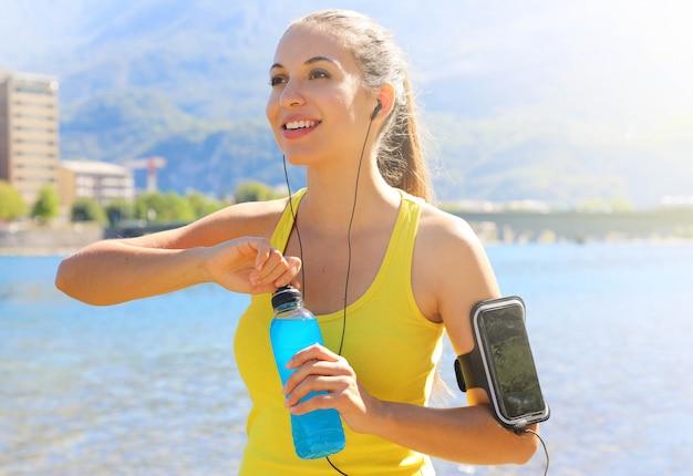 スマートフォンのアームバンドと幸せな陽気な女性アスリートは、毎日のトレーニングと屋外を離れて見てパワードリンクボトルを開きます。
