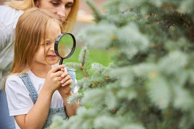 어머니와 함께 야외에서 크리스마스 트리에 돋보기를 통해 찾고 행복 쾌활한 여자 아이