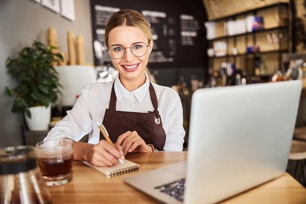 카페에서 사진 카메라를 보고 있는 제복을 입은 행복한 쾌활한 여성