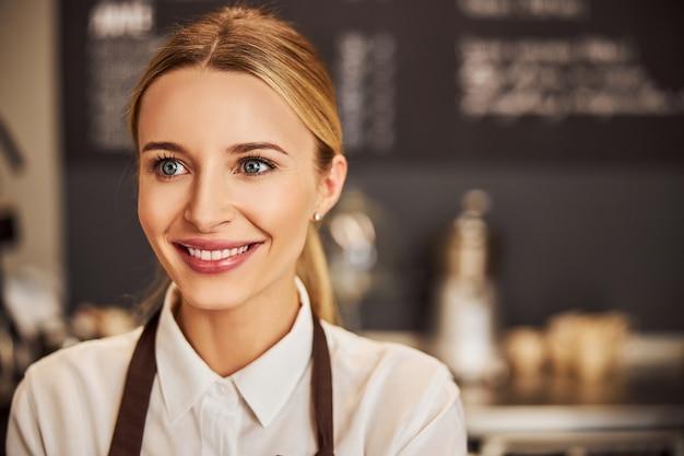 Счастливая жизнерадостная женщина в белой рубашке смотрит в сторону, стоя в помещении