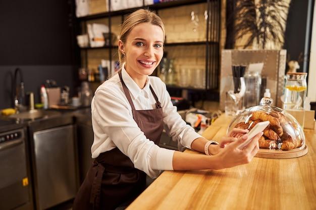 커피 바에서 사진 카메라에 포즈를 취하는 행복한 쾌활한 여성