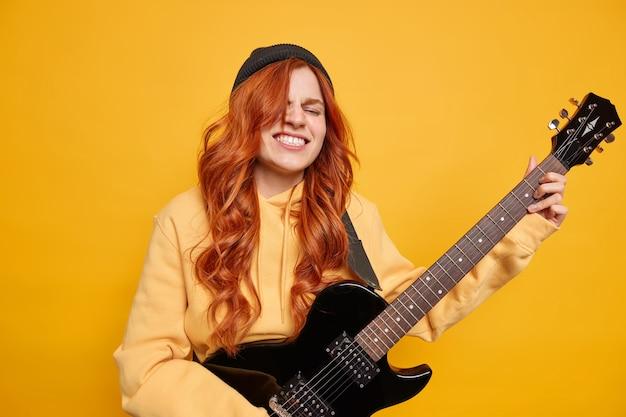 Happy cheerful female teenager has natual long red hair plays black electric guitar in professional studio wears hat casual hoodie