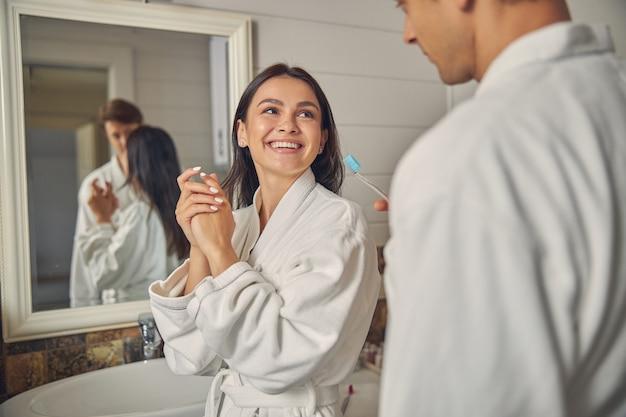 화장실에 서있는 흰색 목욕 가운을 입고 행복 쾌활한 여성
