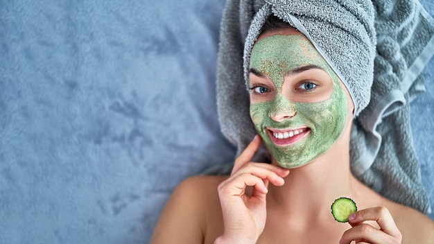 Happy cheerful female with clay mask and cucumber slice in bath towel is resting and relaxing during spa day at home. face skin care