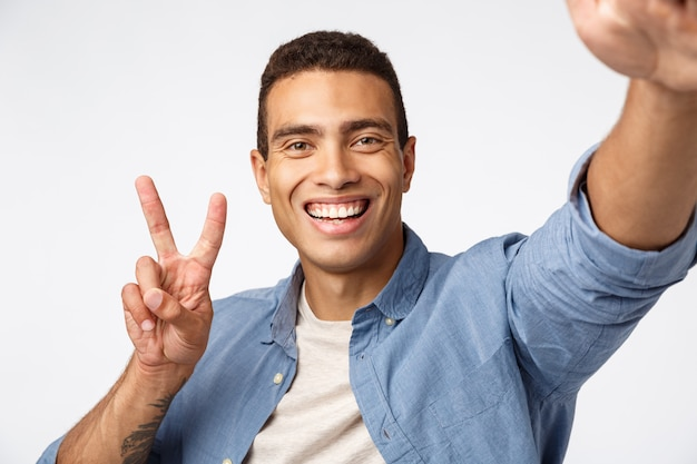 Happy and cheerful friendly man sending positivity, hold camera stretched hand and smiling at smartphone, taking selfie make peace sign, record vlog or talking to girlfriend online,