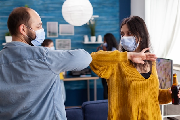 Happy cheerful friends touching elbow keeping social distancing greeting eachother wearing face mask preventing spread of coronavirus holding beer bottles in apartment living room. conceptual image.