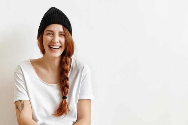 自宅で楽しんでいる間、うれしそうに笑って乱雑な三つ編みで幸せな陽気な生姜10代の少女