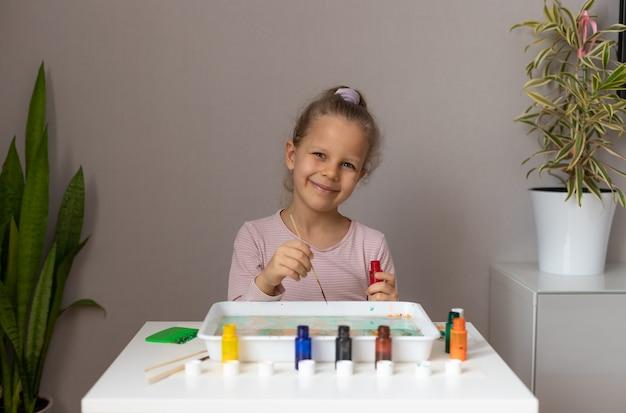 家で墨流しの絵の具で描く幸せな陽気な女の子