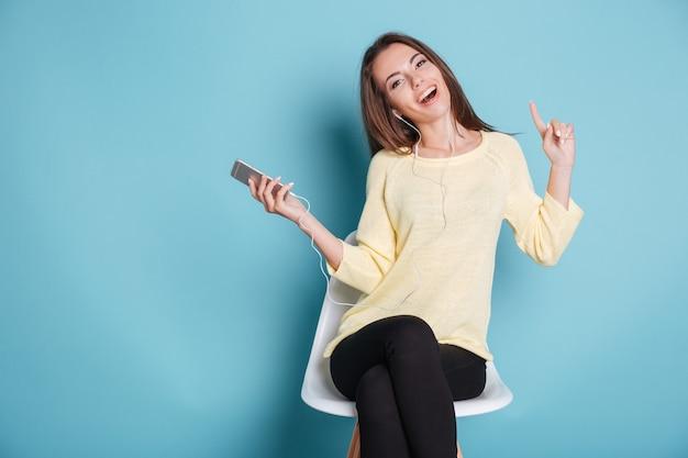 スマートフォンで音楽を聴いて、青い背景で隔離の椅子に座って幸せな陽気な女の子