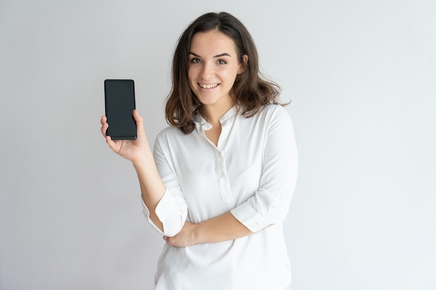 Happy cheerful girl presenting new app on cellphone screen.