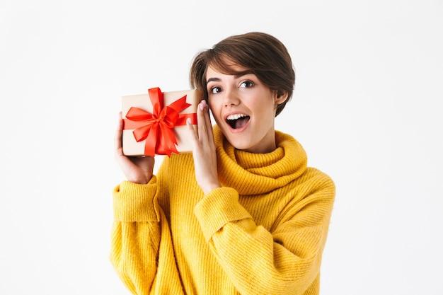 Счастливая жизнерадостная девушка в толстовке с капюшоном, стоящая изолирована на белом, держа подарочную коробку