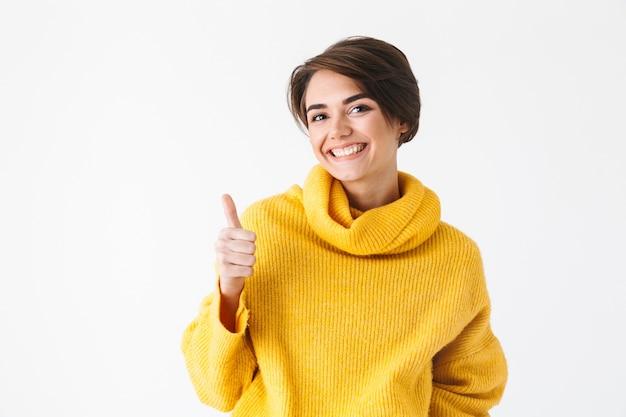 白で隔離、親指を立てて立っているパーカーを着て幸せな陽気な女の子