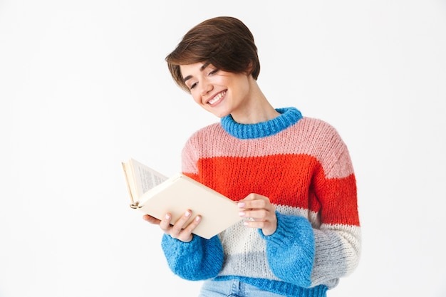 Happy cheerful girl wearing sweater sitting on a chair isolated on white, reading a book