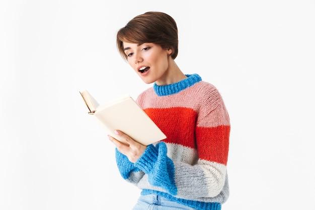 행복 명랑 소녀 스웨터를 입고 흰색에 고립 된 의자에 앉아 책을 읽고