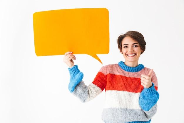 白で隔離のセーターを着て、空の吹き出しを保持して幸せな陽気な女の子