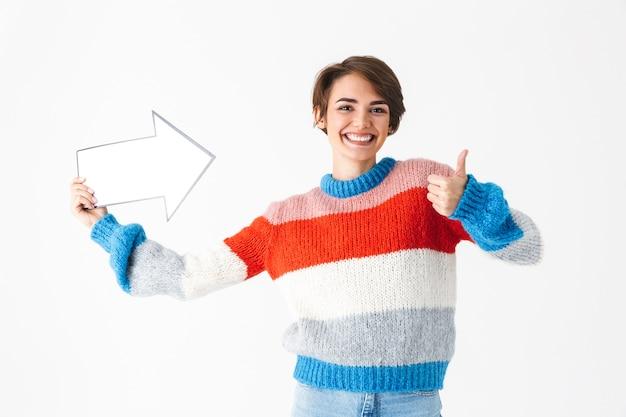 흰색에 고립 된 스웨터 서 입고 행복 명랑 소녀, 종이 화살표로 멀리 가리키는