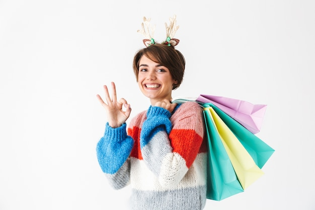 Happy cheerful girl wearing sweater standing isolated on white, carrying shopping bags, ok gesture