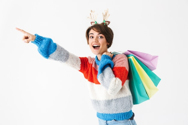 Happy cheerful girl wearing sweater standing isolated on white, carrying shopping bags, pointing away