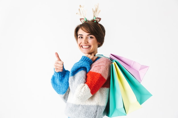 Happy cheerful girl wearing sweater standing isolated on white, carrying shopping bags, thumbs up