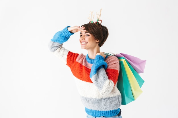 Happy cheerful girl wearing sweater standing isolated on white, carrying shopping bags