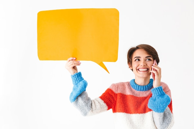 Happy cheerful girl wearing sweater standing isolated on white, holding empty speech bubble, talking on mobile phone