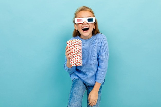 Happy cheerful girl with popcorn and glasses for a movie against a blue wall