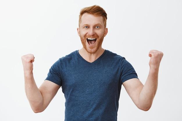 Счастливый веселый красивый рыжий сильный мужчина, поднимающий сжатые кулаки в жесте ура, широко улыбающийся, торжествующий от удачной сделки или отличных новостей, веселый и взволнованный