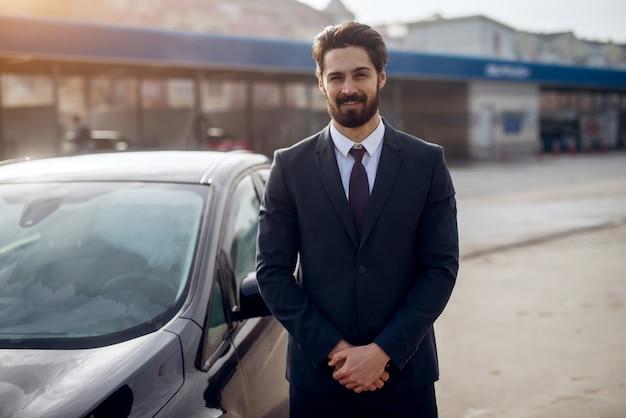 幸せな陽気なハンサムなひげを生やしたスタイリッシュな青年実業家手動洗車セルフサービスステーションで洗浄し、カメラを見て彼の車の横に立っています。