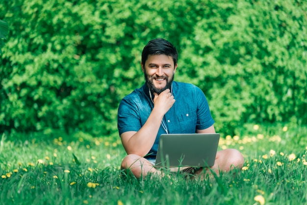 Happy cheerful hipster man with a laptop sitting outdoors on green grass