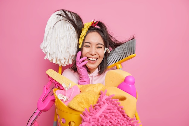 Happy cheerful housewife foolishes around while doing house cleanup surrounded by cleaning supplies basket full of dirty clothes to wash isolated over pink background. household laundering concept