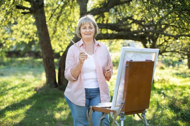 幸せな陽気な陽気な引退した 50 歳の女性アーティストは、イーゼルとブラシを持ち、晴れた朝、緑の春の庭で屋外で絵を描きました。趣味、インスピレーション、レジャーのコンセプト。