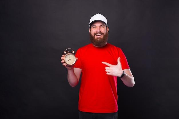 Happy cheerful joyful bearded man pointing at alarm clock over black background