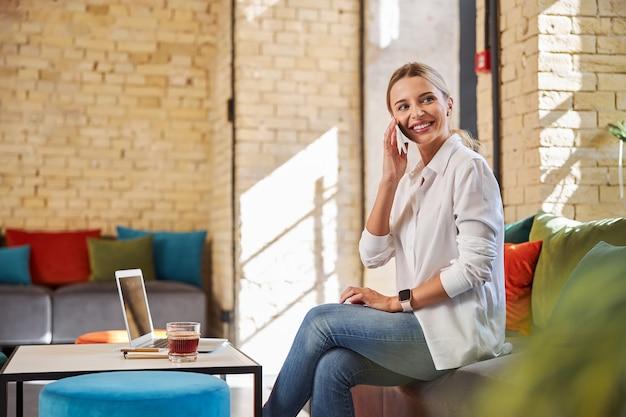 실내에서 휴대전화로 통화하는 흰 블라우스를 입은 행복한 쾌활한 여성