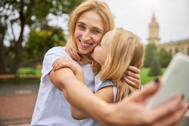 야외에서 함께 시간을 즐기는 딸과 함께 흰 셔츠에 행복 쾌활한 아가씨
