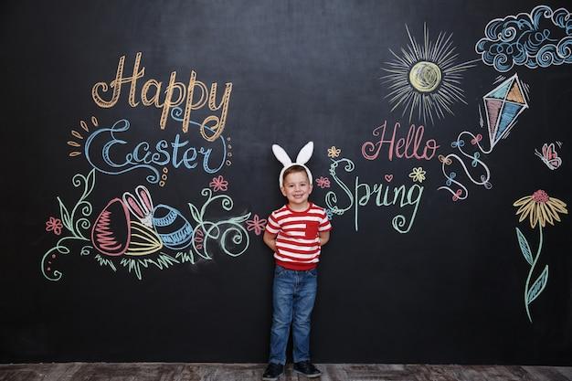 バニーの耳を着てイースターを祝う幸せな陽気な小さな男の子