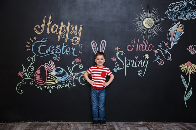 Happy cheerful little boy wearing bunny ears and celebrating easter