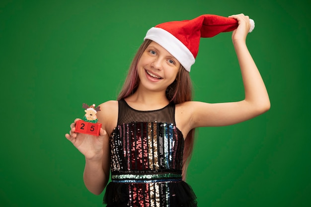 Happy and cheerful little girl in glitter party dress and santa hat showing toy cubes with date twenty five smiling touching her hat standing over green background