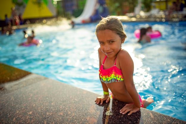 Счастливая жизнерадостная маленькая девочка в цветных купальниках выходит из бассейна в теплый солнечный летний день. концепция счастливого детства и семейных праздников
