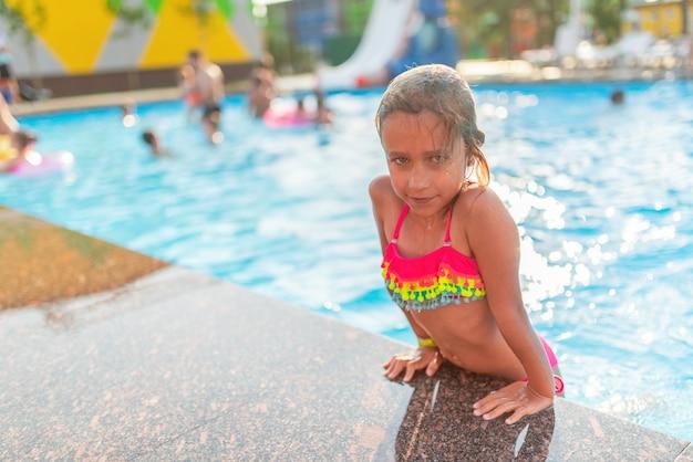 Счастливая жизнерадостная маленькая девочка в цветных купальниках выходит из бассейна в теплый солнечный летний день